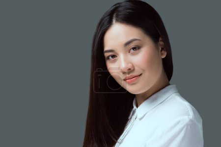 portrait of beautiful young asian woman smiling at camera isolated on grey