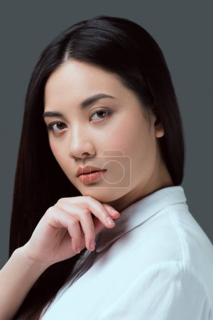 portrait of beautiful young asian woman looking at camera isolated on grey