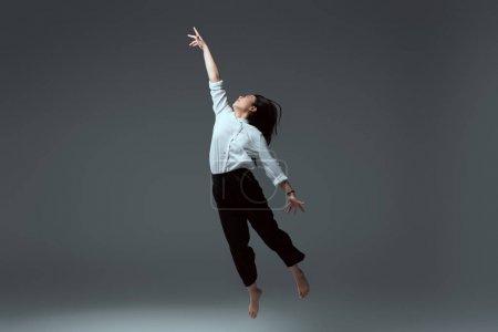 Photo pour Jeune femme aux pieds nus, sautant à main levée sur fond gris - image libre de droit
