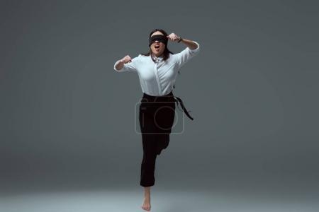 Photo pour Agressive jeune femme pieds nus dans le bandeau noir sauter à pleine bouche sur fond gris - image libre de droit