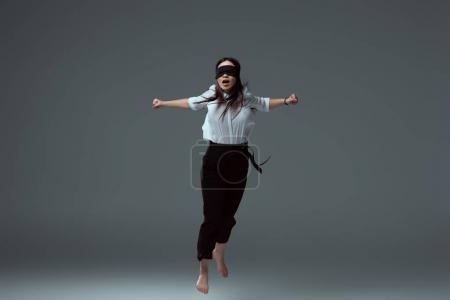 Photo pour Jeune femme aux pieds nus en noir avec les yeux bandés sautant à pleine bouche sur fond gris - image libre de droit