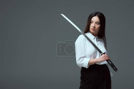 attractive young asian woman holding katana sword and looking away isolated on grey