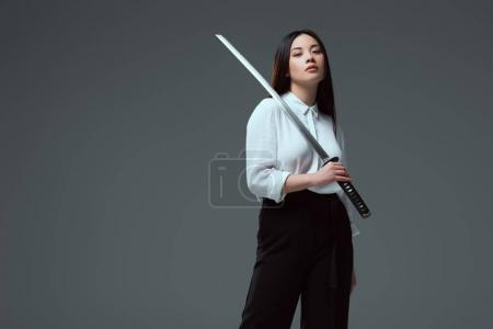 attractive young asian woman holding katana sword and looking at camera isolated on grey