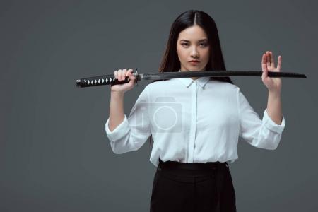 beautiful asian girl holding katana sword and looking at camera isolated on grey