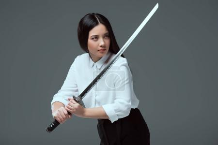 beautiful asian girl holding katana sword and looking away isolated on grey