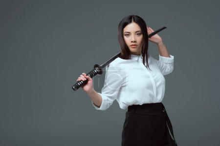 young asian woman holding katana and looking at camera isolated on grey