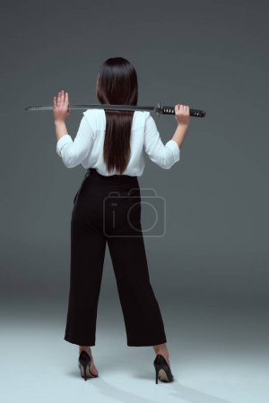 back view of woman holding katana on shoulders on grey