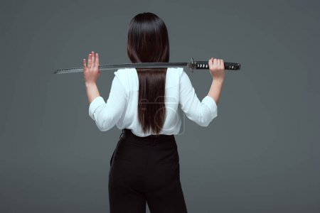 back view of woman holding katana on shoulders isolated on grey