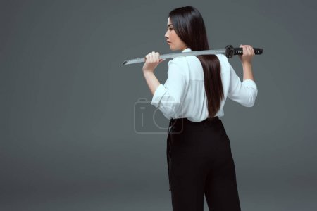 back view of beautiful asian girl holding katana on shoulders isolated on grey