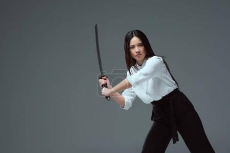 young asian woman fighting with katana sword and looking at camera isolated on grey