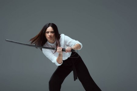 young asian woman fighting with katana sword isolated on grey