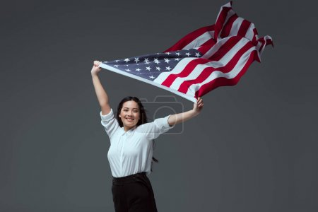 beautiful young woman holding american flag in raised hands and smiling at camera isolated on grey