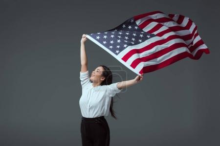 happy young woman holding american flag in raised hands and looking away isolated on grey