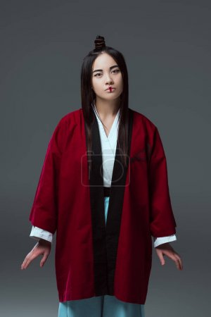 beautiful young asian woman in kimono looking at camera isolated on grey