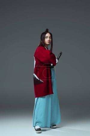young asian woman in kimono holding katana sword and looking at camera on grey