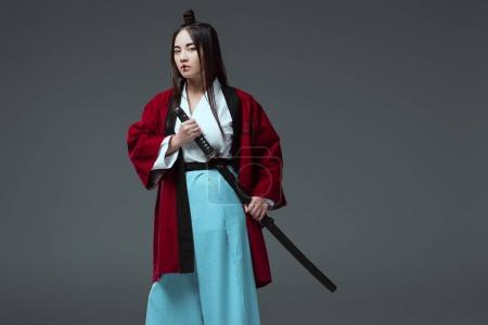 young asian woman in kimono holding katana sword and looking at camera isolated on grey