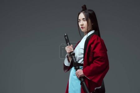 young asian woman in kimono holding katana and looking away isolated on grey