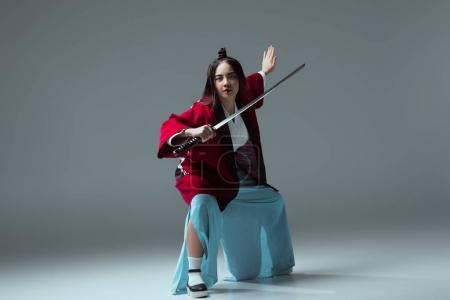 asian woman in kimono fighting with katana sword and looking at camera on grey