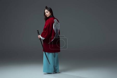 Photo for Back view of samurai in kimono holding katana and looking at camera on grey - Royalty Free Image