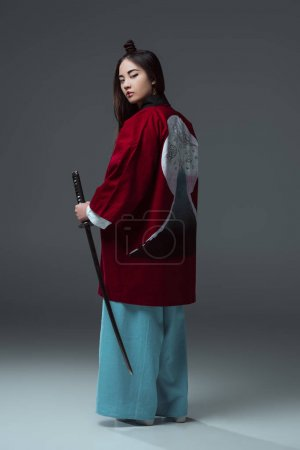 back view of woman in traditional japanese kimono holding katana and looking at camera on grey