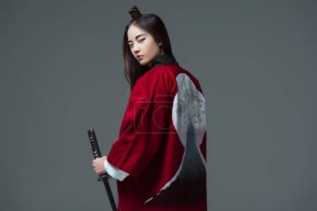 Photo for Young woman in traditional japanese kimono holding katana and looking at camera isolated on grey - Royalty Free Image