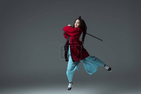 asian woman in kimono fighting with katana in jump on grey
