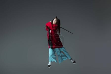 young woman in kimono fighting with katana in jump isolated on grey