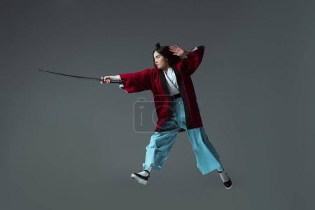 full length view of samurai in kimono fighting with katana in jump isolated on grey
