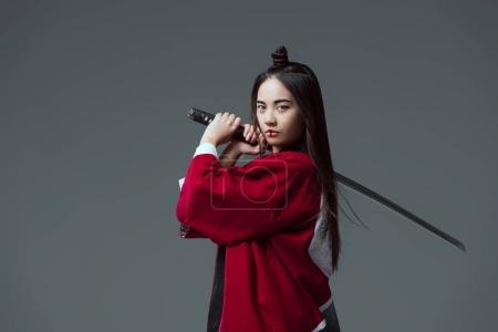 young woman in kimono holding katana and looking at camera isolated on grey