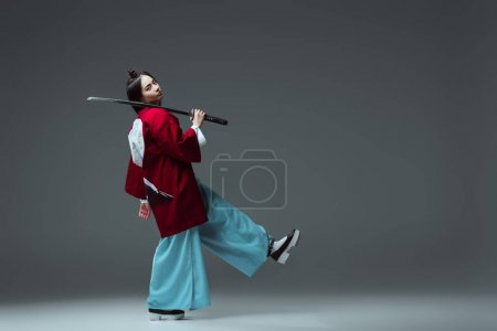 side view of samurai in kimono walking with katana and looking at camera on grey
