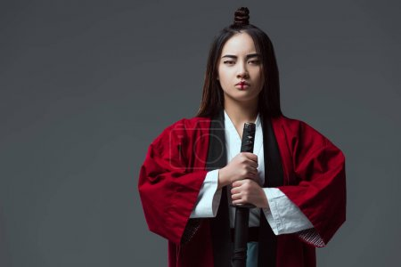 Photo for Asian woman in kimono holding katana sword and looking at camera isolated on grey - Royalty Free Image