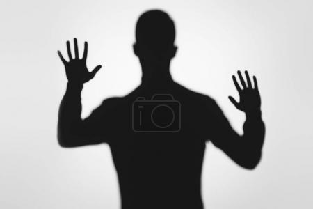 mysterious blurry shadow of person raising hands on grey