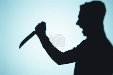 shadow of person screaming and holding knife on blue