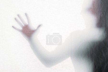 blurry silhouette of screaming person touching frosted glass