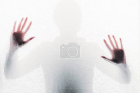 blurry silhouette of person touching frosted glass with hands