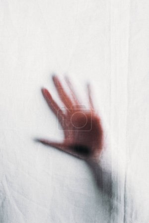 Photo for Blurry silhouette of human hand touching veil - Royalty Free Image