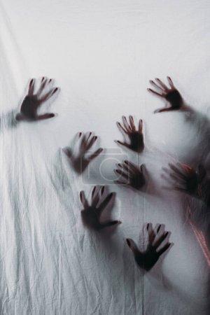 Photo pour Floues silhouettes effrayants de mains humaines touchant en verre dépoli - image libre de droit