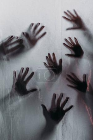 Blurry scary silhouettes of human hands touching f...