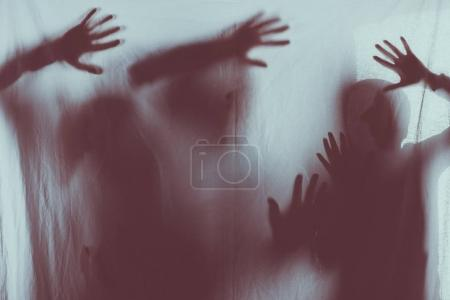 blurry scary silhouettes of people touching frosted glass with hands
