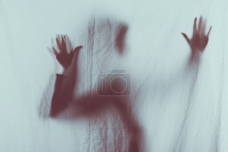Photo for Scary blurry silhouette of person touching veil with hands - Royalty Free Image