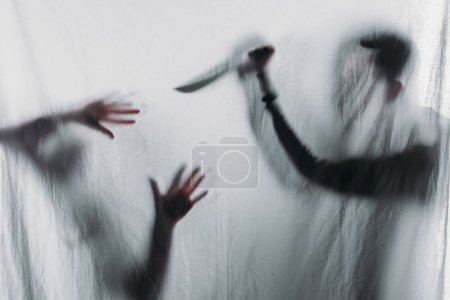 Photo for Silhouette of someone holding knife and murdering victim, crime concept - Royalty Free Image