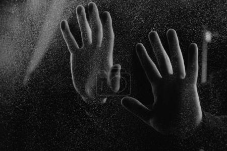 cropped shot of person touching frosted glass with palms in darkness