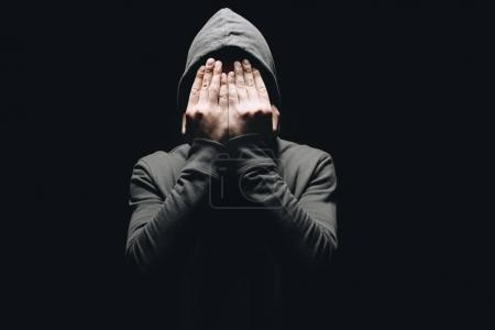Photo for Cropped shot of man in hoodie closing eyes with hands isolated on black - Royalty Free Image