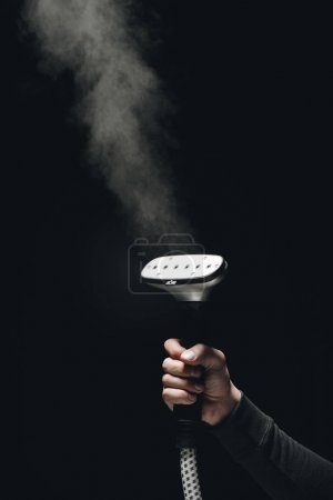Photo for Close-up partial view of person holding garment steamer with steam on black - Royalty Free Image