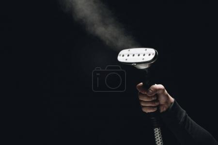 Photo for Cropped shot of person holding garment steamer with steam on black - Royalty Free Image