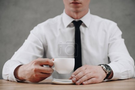 cropped shot of businessman holding cup of coffee on grey