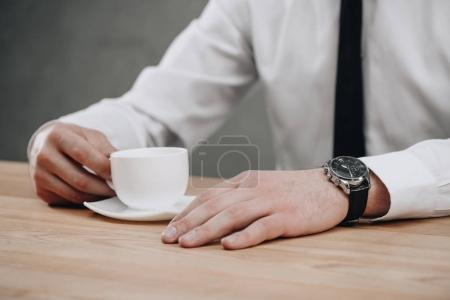 close-up partial view of businessman holding cup of coffee