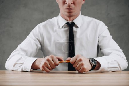 mid section of businessman holding broken pencil in hands