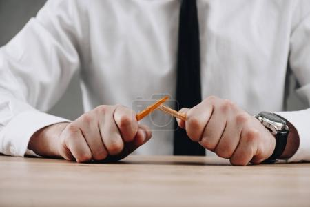 cropped shot of businessman holding broken pencil in hands