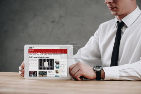 Photo for Cropped shot of businessman holding digital tablet with BBC news website on screen - Royalty Free Image